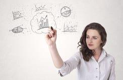 Νέα κυρία που σκιαγραφεί τα οικονομικά εικονίδια και τα σύμβολα διαγραμμάτων Στοκ Εικόνα