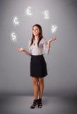 Νέα κυρία που στέκεται και που κάνει ταχυδακτυλουργίες με τα εικονίδια νομίσματος Στοκ Εικόνα