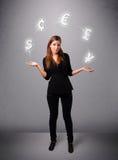 Νέα κυρία που στέκεται και που κάνει ταχυδακτυλουργίες με τα εικονίδια νομίσματος Στοκ Φωτογραφία