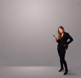 Νέα κυρία που στέκεται και που κρατά ένα τηλέφωνο με το διάστημα αντιγράφων Στοκ Εικόνες