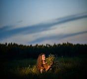 Νέα κυρία σε ένα κεντημένο φόρεμα με μια ανθοδέσμη των wildflowers Στοκ φωτογραφίες με δικαίωμα ελεύθερης χρήσης