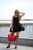 Νέα κυρία στο φόρεμα κοκτέιλ και τα ψηλοτάκουνα παπούτσια που θέτουν το outdoo Στοκ Φωτογραφίες