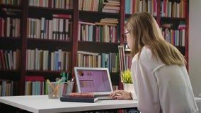Νέα κυρία Using ένα lap-top στη βιβλιοθήκη απόθεμα βίντεο