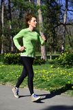 Νέα κόκκινη κυρία τρίχας στο πράσινο πουκάμισο που κάνει την κατάρτιση τρεξίματός της στο πάρκο στοκ εικόνα
