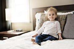Νέα κόρη δύο χρονών που χαλαρώνει στο κρεβάτι, θετικά συναισθήματα στοκ εικόνες