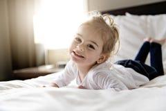 Νέα κόρη δύο χρονών που χαλαρώνει στο κρεβάτι, θετικά συναισθήματα στοκ φωτογραφία με δικαίωμα ελεύθερης χρήσης