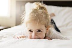 Νέα κόρη δύο χρονών που χαλαρώνει στο κρεβάτι, θετικά συναισθήματα στοκ εικόνες με δικαίωμα ελεύθερης χρήσης