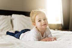 Νέα κόρη δύο χρονών που χαλαρώνει στο κρεβάτι, θετικά συναισθήματα στοκ φωτογραφία