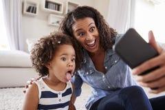 Νέα κόρη μητέρων και μικρών παιδιών που παίρνει selfie στο σπίτι στοκ φωτογραφίες με δικαίωμα ελεύθερης χρήσης
