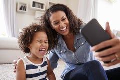 Νέα κόρη μητέρων και μικρών παιδιών που παίρνει selfie στο σπίτι στοκ εικόνες με δικαίωμα ελεύθερης χρήσης
