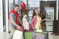 Νέα κόρη ώθησης πατέρων και μητέρων στο καροτσάκι αγορών μέσω της λεωφόρου Στοκ Εικόνες