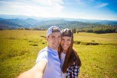 Νέα λήψη πεζοπορίας ζευγών selfie με το έξυπνο τηλέφωνο Ευτυχείς νεαρός άνδρας και γυναίκα που παίρνουν την αυτοπροσωπογραφία με  στοκ εικόνα