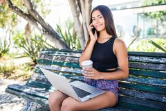 Νέα λατινική συνεδρίαση γυναικών στον πάγκο, που μιλά στο smartphone, που λειτουργεί στο lap-top υπαίθρια Τεχνολογία, επικοινωνία στοκ φωτογραφία με δικαίωμα ελεύθερης χρήσης