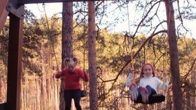 Νέα λατρευτά κορίτσια που έχουν τη διασκέδαση στην ταλάντευση στο πάρκο φθινοπώρου φιλμ μικρού μήκους