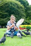 Νέα λατρευτά ταΐζοντας περιστέρια κοριτσιών το σκωτσέζικο καλοκαίρι πράσινη ισοτιμία Στοκ Φωτογραφία