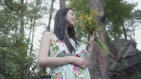 Νέα λατρευτή γυναίκα πορτρέτου με τη μακριά μαύρη στάση τρίχας στα ξύλινα σκαλοπάτια και τα άγρια λουλούδια μυρωδιών στην κατάπλη απόθεμα βίντεο