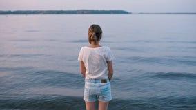 Νέα λεπτή γυναίκα που εξετάζει το νερό και που σκέφτεται στο ηλιοβασίλεμα απόθεμα βίντεο