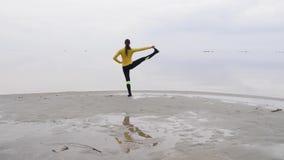 Νέα λεπτή γυναίκα που κάνει την άσκηση γιόγκας ικανότητας στην παραλία θάλασσας στο ηλιοβασίλεμα Άνευ ραφής υπόβαθρο φύσης του ου φιλμ μικρού μήκους