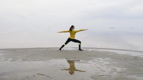 Νέα λεπτή γυναίκα που κάνει την άσκηση γιόγκας ικανότητας στην παραλία θάλασσας στο ηλιοβασίλεμα Άνευ ραφής υπόβαθρο φύσης του ου απόθεμα βίντεο