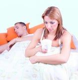 Νέα λυπημένη συνεδρίαση γυναικών στο σπορείο, κοντινός κοιμησμένος άνδρας στοκ εικόνες