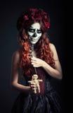 Νέα μάγισσα βουντού με τα muertos makeup & x28 ζάχαρη skull& x29  κρατά την κούκλα και τη βελόνα βουντού Στοκ Εικόνες