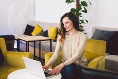 Νέα μέση ηλικίας καυκάσια γυναίκα με μακρυμάλλη Περιστασιακά ενδύματα που χρησιμοποιούν το φορητό προσωπικό υπολογιστή στο εσωτερ στοκ φωτογραφίες με δικαίωμα ελεύθερης χρήσης