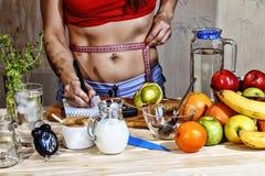 Νέα μέτρα γυναικών detox Το νέο κορίτσι μετρά τη μέση και χρησιμοποιεί την κατάλληλη διατροφή Ποτά Detox, συστατικά, αλτήρες Conc στοκ φωτογραφίες