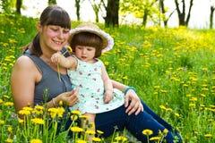 Νέα μαμά και το μωρό της που βάζουν στη χλόη και το αγκάλιασμα Στοκ Εικόνα