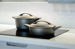 Νέα μαύρα τηγάνια Η έννοια του σύγχρονου εσωτερικού κουζινών στοκ εικόνες
