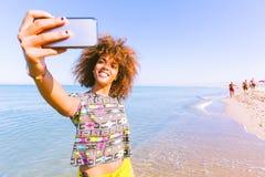 Νέα μαύρη γυναίκα που παίρνει ένα selfie στην παραλία Στοκ φωτογραφίες με δικαίωμα ελεύθερης χρήσης