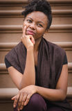 Νέα μαύρη γυναικεία συνεδρίαση στη σκέψη βημάτων Στοκ Φωτογραφίες