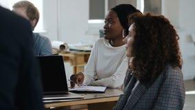 Νέα μαύρη επαγγελματική εταιρική γυναίκα διευθυντών που ακούει στη συζήτηση ομάδων στον πίνακα στο multiethnic σύγχρονο γραφείο φιλμ μικρού μήκους