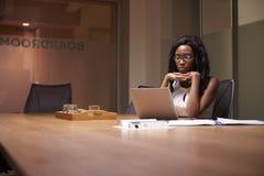 Νέα μαύρη επιχειρηματίας που απασχολείται αργά μόνο σε στην αρχή στοκ εικόνα
