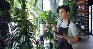 Νέα μετρώντας λουλούδια επιχειρηματιών στο floral κατάστημα και χρησιμοποίηση της ταμπλέτας στην εργασία