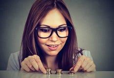 Νέα μετρώντας χρήματα γυναικών που συσσωρεύουν επάνω τα νομίσματα Στοκ εικόνα με δικαίωμα ελεύθερης χρήσης