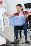 Νέα με ειδικές ανάγκες γυναίκα στην αναπηρική καρέκλα που κάνει το πλυντήριο Στοκ Εικόνες