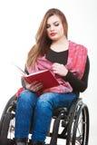 Νέα με ειδικές ανάγκες γυναίκα στην αναπηρική καρέκλα με το βιβλίο Στοκ εικόνα με δικαίωμα ελεύθερης χρήσης
