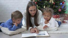 Νέα μητέρα άλλη με δύο παιδιά που διαβάζουν ένα βιβλίο στο πάτωμα κοντά στο χριστουγεννιάτικο δέντρο φιλμ μικρού μήκους