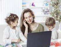 Νέα μητέρα - επιχειρησιακή γυναίκα που εργάζεται στο lap-top και που μιλά στο smartphone εκτός από τα παιδιά τους Στοκ Εικόνα
