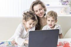 Νέα μητέρα - επιχειρησιακή γυναίκα που εργάζεται στο lap-top και που μιλά στο smartphone εκτός από τα παιδιά τους Στοκ εικόνες με δικαίωμα ελεύθερης χρήσης