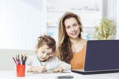 Νέα μητέρα - η επιχειρησιακή γυναίκα που εργάζεται στο lap-top και την πενταετή παλαιά κόρη της σύρει με τα κραγιόνια Στοκ εικόνα με δικαίωμα ελεύθερης χρήσης