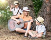 Νέα μητέρα και δύο γιοι στηρίζονται στα ξύλα, που τραγουδούν τα τραγούδια με μια κιθάρα στοκ φωτογραφία