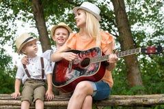 Νέα μητέρα και δύο γιοι στηρίζονται στα ξύλα, που τραγουδούν τα τραγούδια με μια κιθάρα στοκ εικόνα με δικαίωμα ελεύθερης χρήσης
