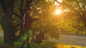 Νέα μητέρα και η κόρη παιδιών της που ταλαντεύονται στην ταλάντευση και που γελούν ένα θερμό βράδυ φθινοπώρου υπαίθρια Ευτυχής αγ απόθεμα βίντεο
