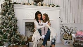 Νέα μητέρα και η κόρη της που καθίστανται άνετος σε μια καρέκλα κοντά στην εστία φιλμ μικρού μήκους