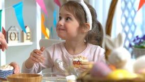 Νέα μητέρα και η κόρη της που φορούν τα αυτιά λαγουδάκι που μαγειρεύουν Πάσχα cupcakes απόθεμα βίντεο