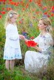Νέα μητέρα και κορίτσι παιδιών στα άσπρα φορέματα στο θερινό λιβάδι Dau Στοκ Εικόνες