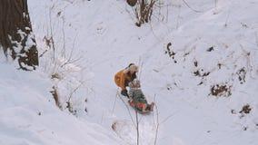 Νέα μητέρα και λίγη κόρη που έχουν τη διασκέδαση στο έλκηθρο στο χειμερινό πάρκο φιλμ μικρού μήκους
