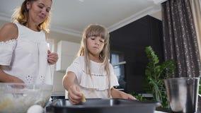 Νέα μητέρα και λίγη κόρη που κατασκευάζουν τα μπισκότα στην κουζίνα Γυναίκα και μικρό κορίτσι στην κουζίνα που τοποθετούν τη ζύμη απόθεμα βίντεο