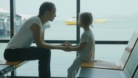 Νέα μητέρα και λίγη κόρη που περιμένουν ένα ταξίδι στο σαλόνι θαλάσσιων λιμένων απόθεμα βίντεο